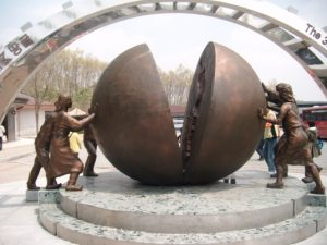 Photo of statue at DMZ, people pushing two halves of a ball together